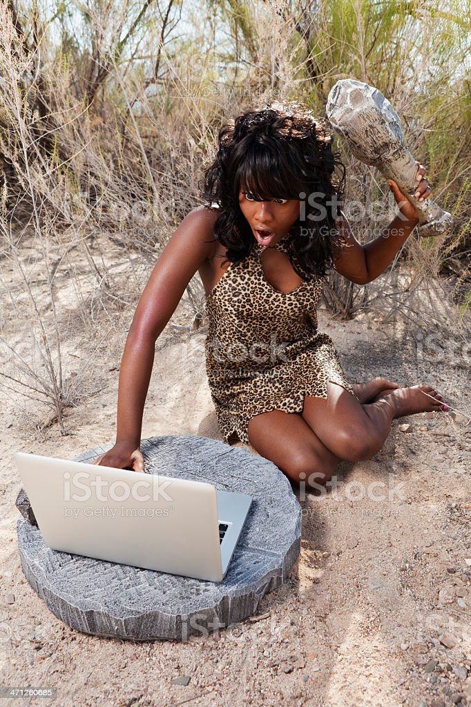 Scared cavewoman about to hit laptop with club stock photo