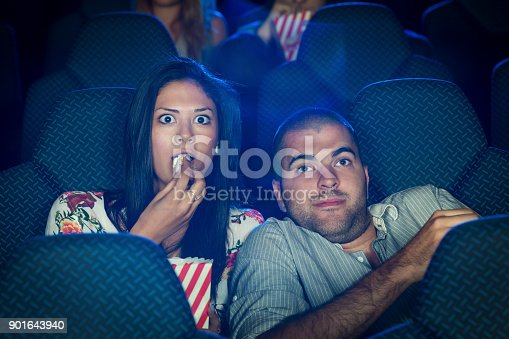 Young couple watching a horror movie in a cinema. Scared people, both Caucasian, casual, about 25 years old.