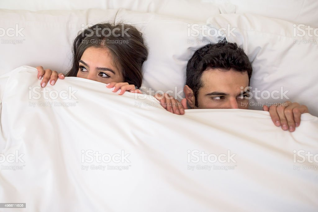 Scared couple in bed stock photo