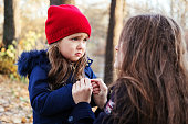 Scared daughter holding mother's hands in autumn park. Child girl express sad emotions, complain about their own problems