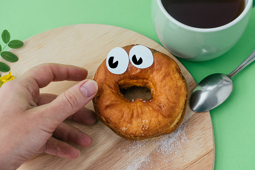Scared doughnut with paper eyes lies on a wooden cutting board next to a mug of tea.The hand reaches out to eat it.Creative minimal food concept.National donut day