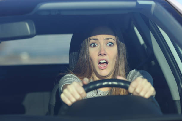 Scared driver driving a car before an accident stock photo
