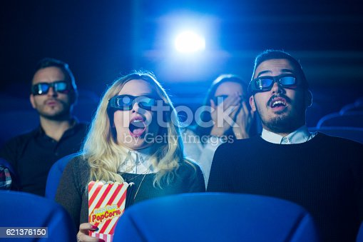 istock Scared friends at movie theatre 621376150