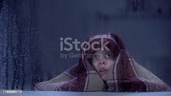 Scared girl covered in blanket frightened of ghost, fears and phobias concept