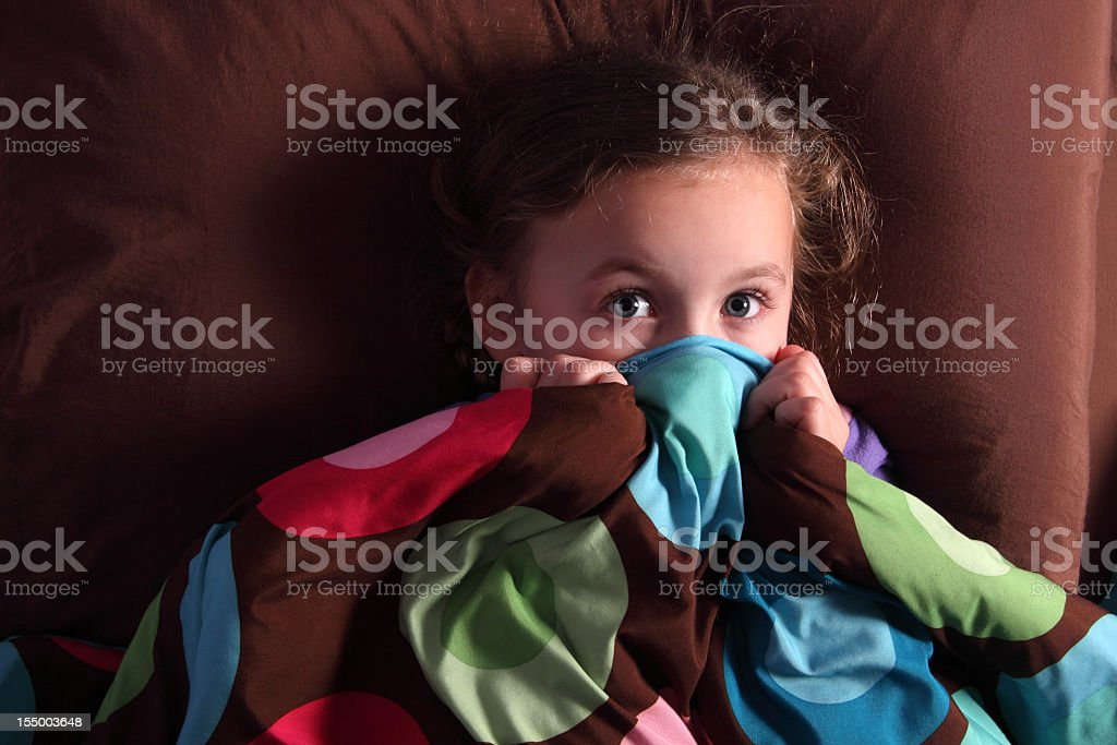 Scared girl covering mouth with covers royalty-free stock photo