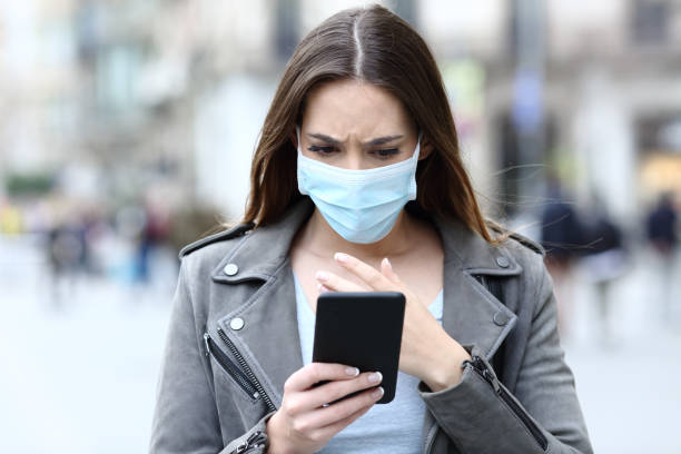 Scared girl with mask reading news on her phone on street stock photo