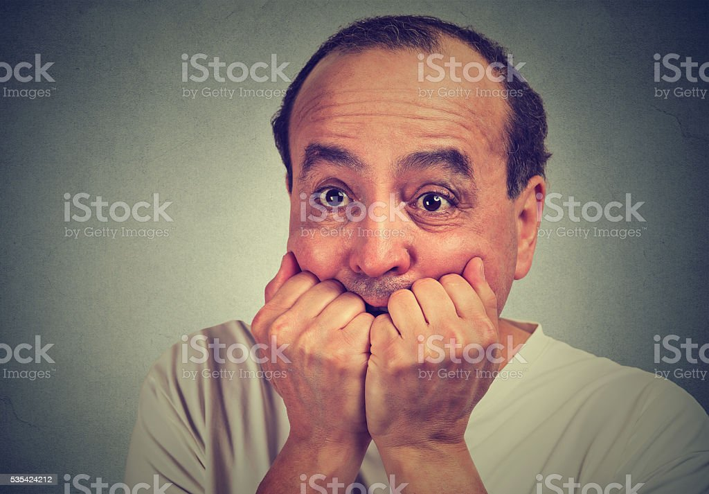 scared guy biting his nails looking anxious in panic stock photo