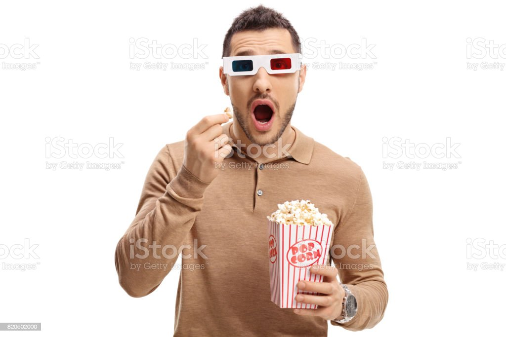 Scared guy with a pair of 3D glasses and popcorn stock photo