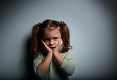 Scared kid girl with hands near face looking with horror on dark background with empty space for text