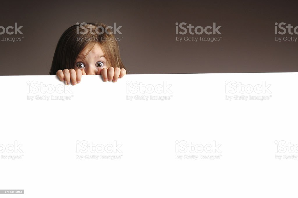 Scared Little Girl Peeking from Behind Blank Sign royalty-free stock photo