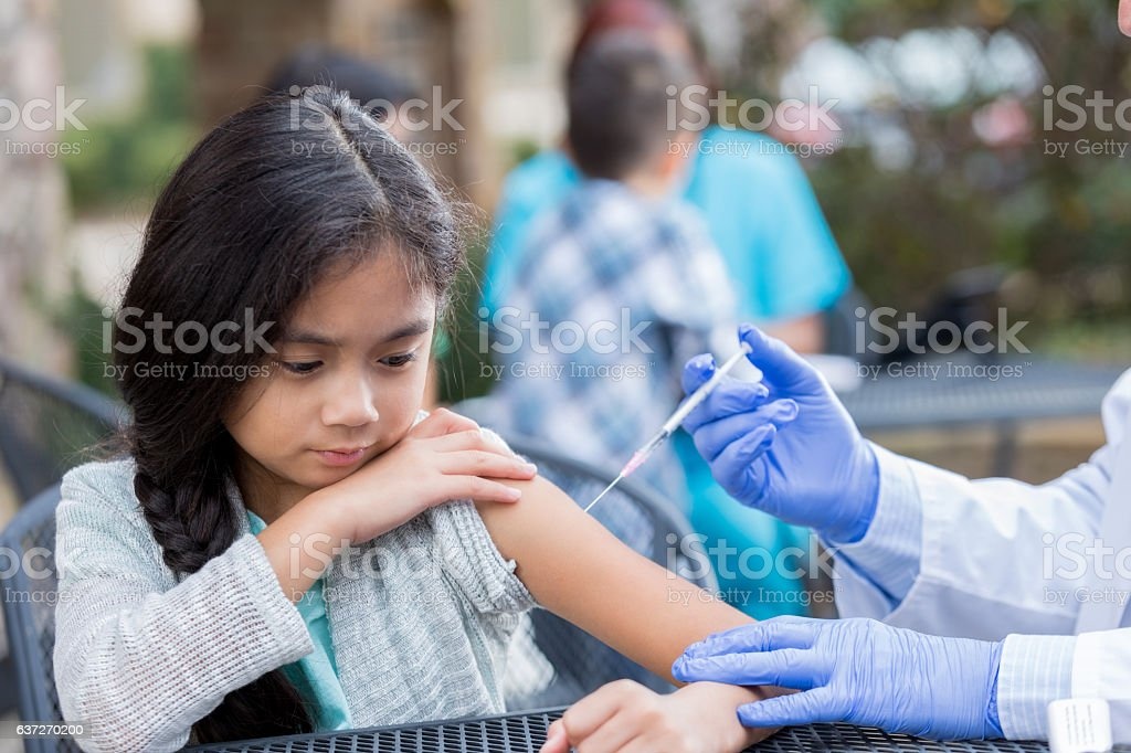 Scared little girl receives immunization at outdoor health clinic stock photo