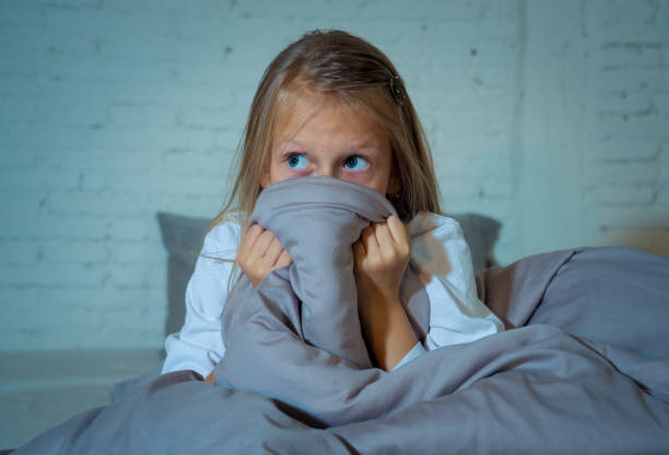 scared little girl staying sleepless hiding behind the duvet looking horrified in the dark having childhood nightmares in child imagination sleeping disorders stress depression and insomnia concept. - fear stock photos and pictures