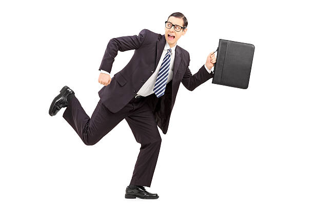 Scared male businessman running away from something stock photo