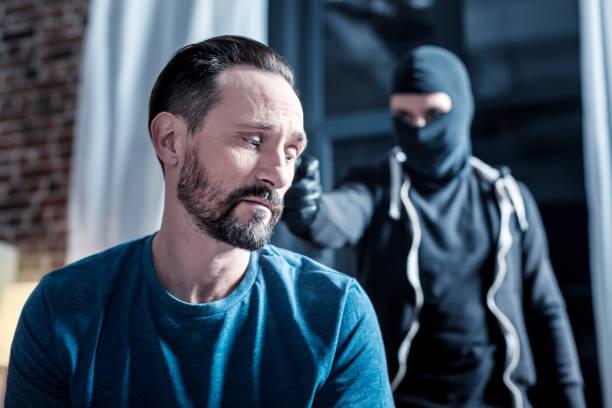 Homem com medo e um criminoso armado atrás dele - foto de acervo
