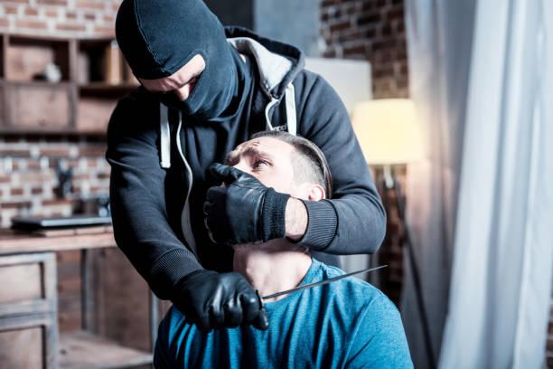 Homem com medo e assassino segurando a faca no pescoço dele - foto de acervo
