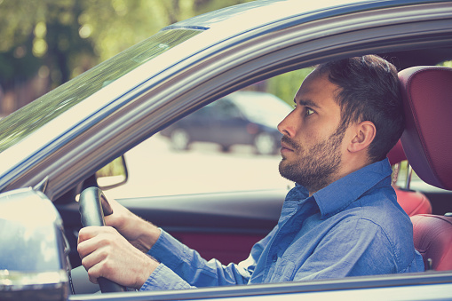 istock scared man driver in car. Inexperienced anxious motorist 586708650