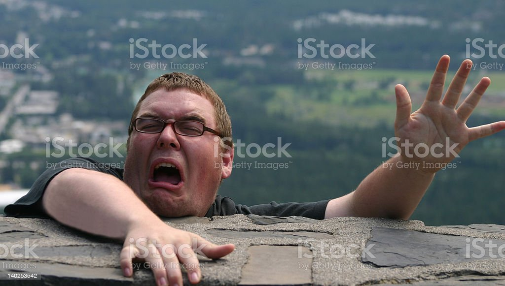 Scared Man Hanging from Ledge stock photo