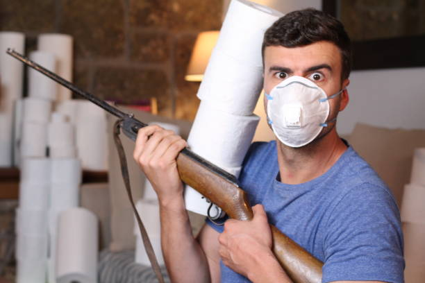 Homem assustado segurando arma durante quarentena - foto de acervo