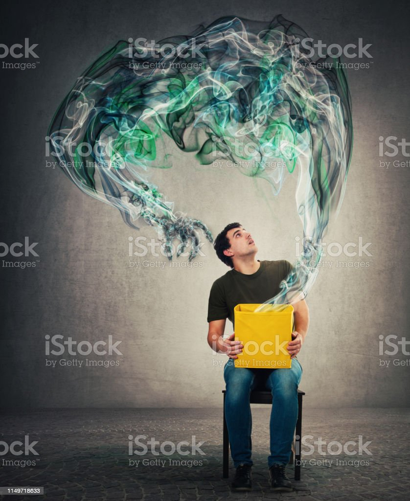Scared man seated on a chair holding mystery box on knees looking up...