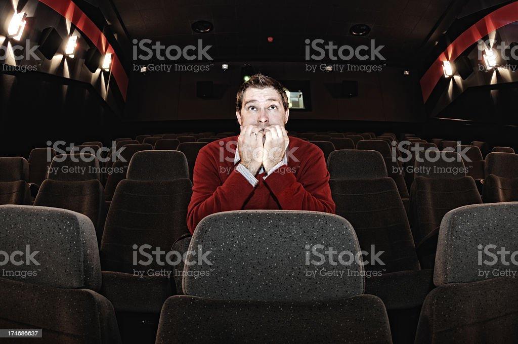Scared Man Sitting in Movie Theatre Alone stock photo