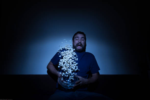 Scared man watching a horror movie and jumping with popcorn flying allover stock photo
