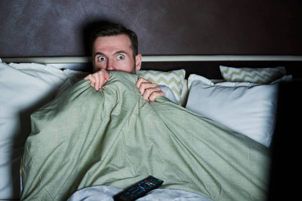 scared man watching horror movies at night - horror stock pictures, royalty-free photos & images