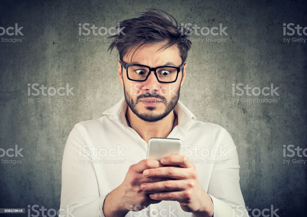 Scared man watching social media stock photo