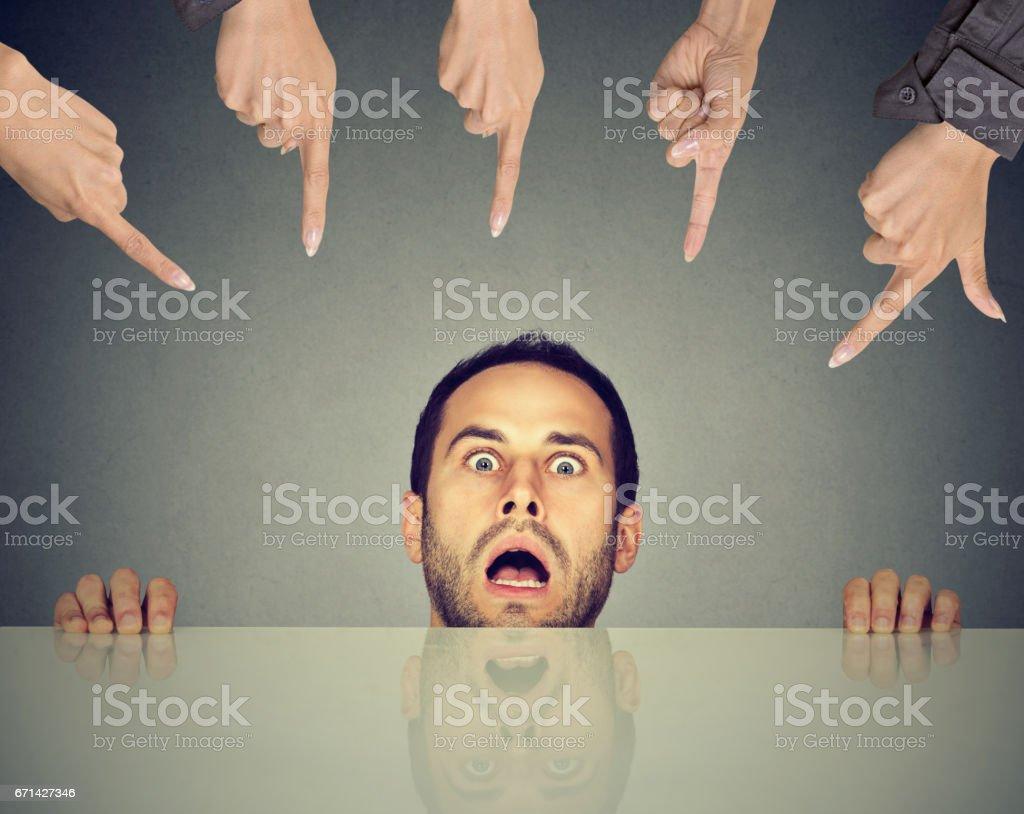 Assustou o jovem empregado de homem escondido debaixo da mesa, sendo acusada por muitas pessoas que apontam os dedos para ele - foto de acervo