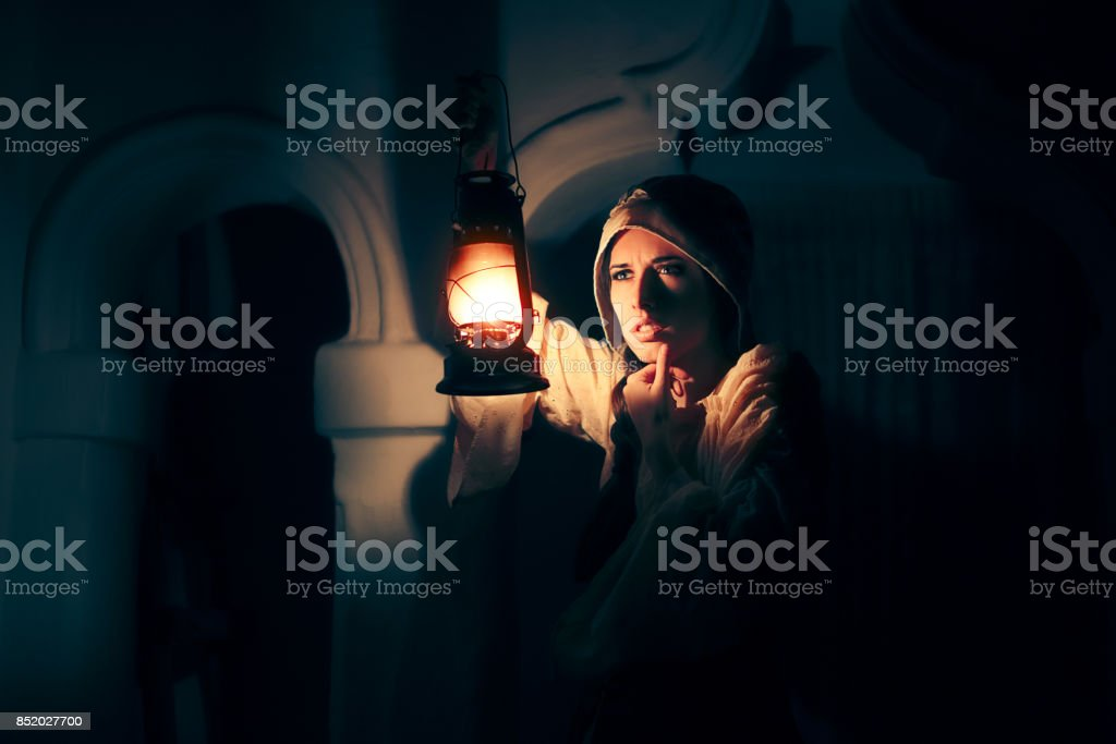 Scared Medieval Woman with Vintage Lantern Outside at Night stock photo