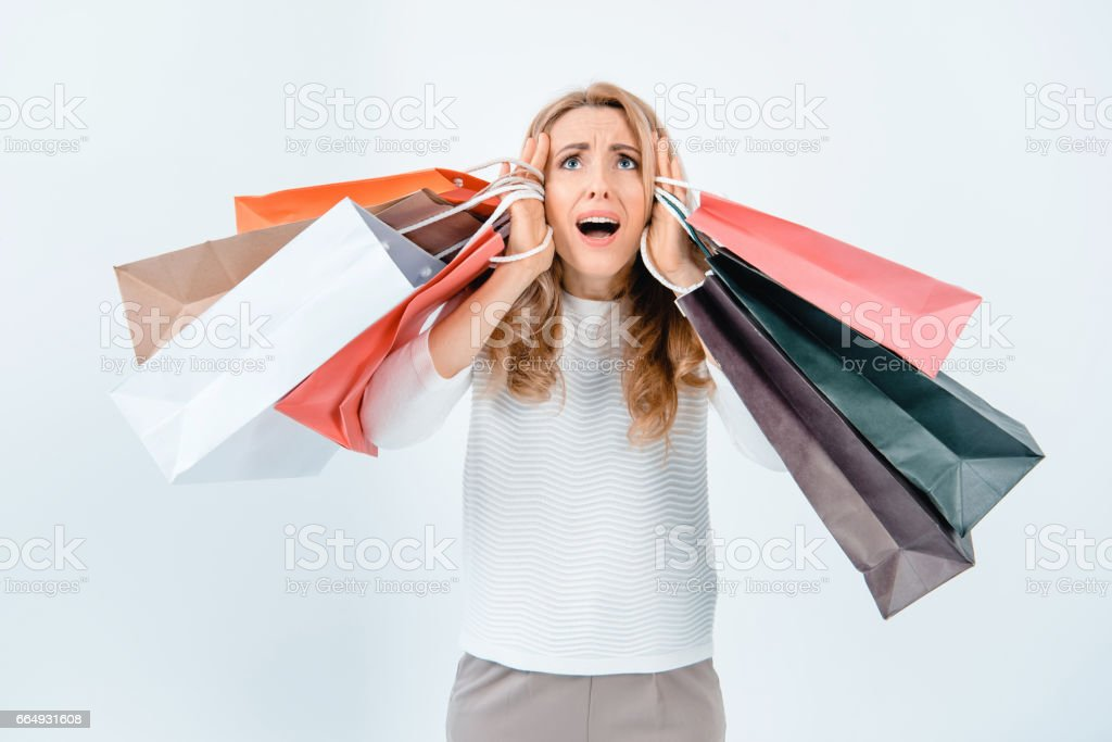 Scared middle aged woman holding shopping bags and looking up on grey stock photo