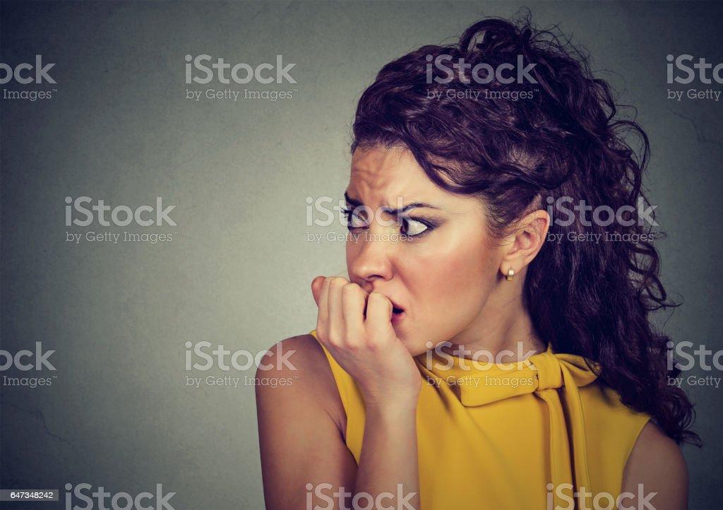 scared nervous woman biting fingernails craving for something stock photo