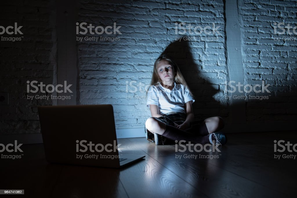 Scared sad girl bullied on line with laptop suffering cyberbullying and harassment feeling desperate and intimidated. Child victim of bullying stalker social media network royalty-free stock photo