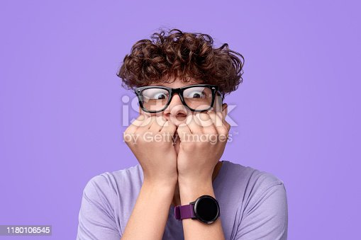 Shocked youngster in glasses biting nails and looking at camera in fear against bright purple background