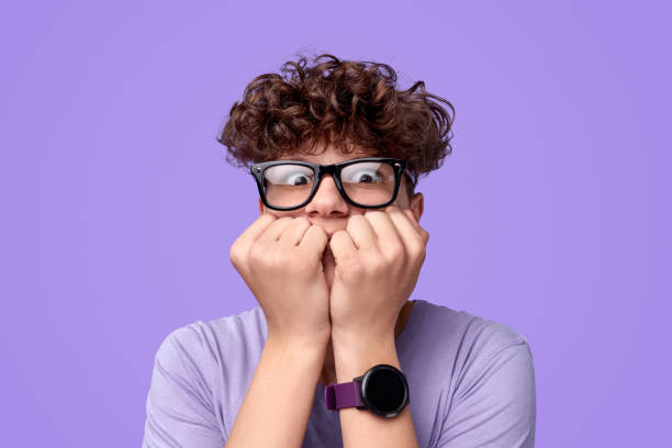 Scared teenager biting nails Shocked youngster in glasses biting nails and looking at camera in fear against bright purple background fear stock pictures, royalty-free photos & images