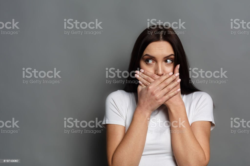 Scared woman covering mouth with hands stock photo