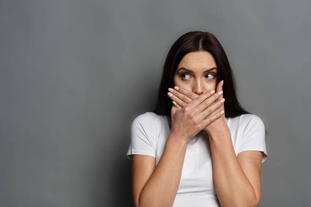 scared woman covering mouth with hands - covering stock photos and pictures