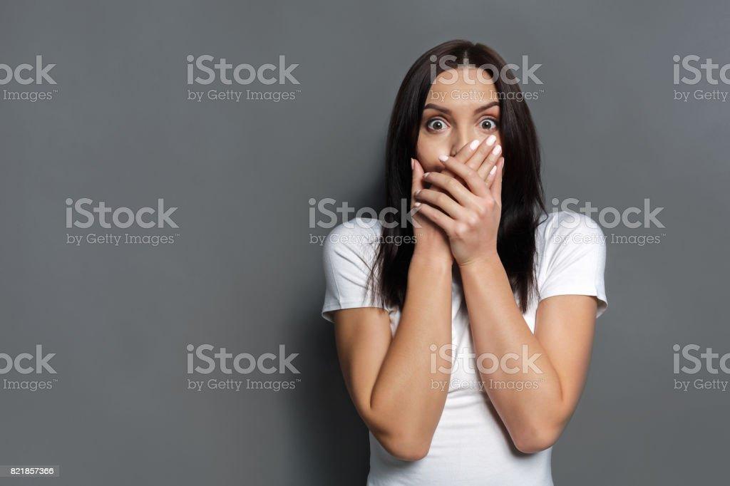 Mujer asustada que cubre la boca con las manos - foto de stock