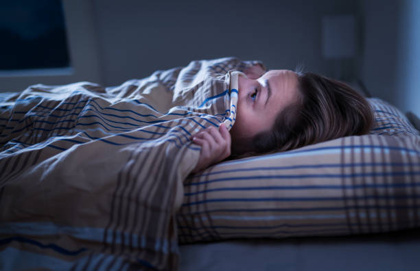 przerażona kobieta ukrywa się pod kocem. boi się ciemności. nie można spać po koszmarze lub złym śnie. obudź się w środku nocy w sypialni w domu.  potwór pod łóżkiem. - horror zdjęcia i obrazy z banku zdjęć