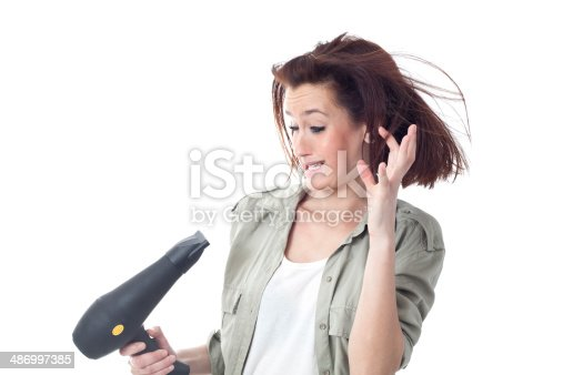 639833996istockphoto Scared woman holding hair dryer 486997385