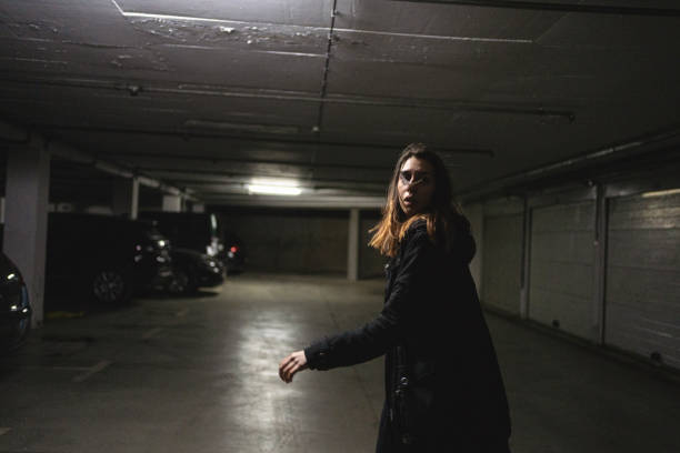 Scared woman running away from her abused in an underground parking lot stock photo