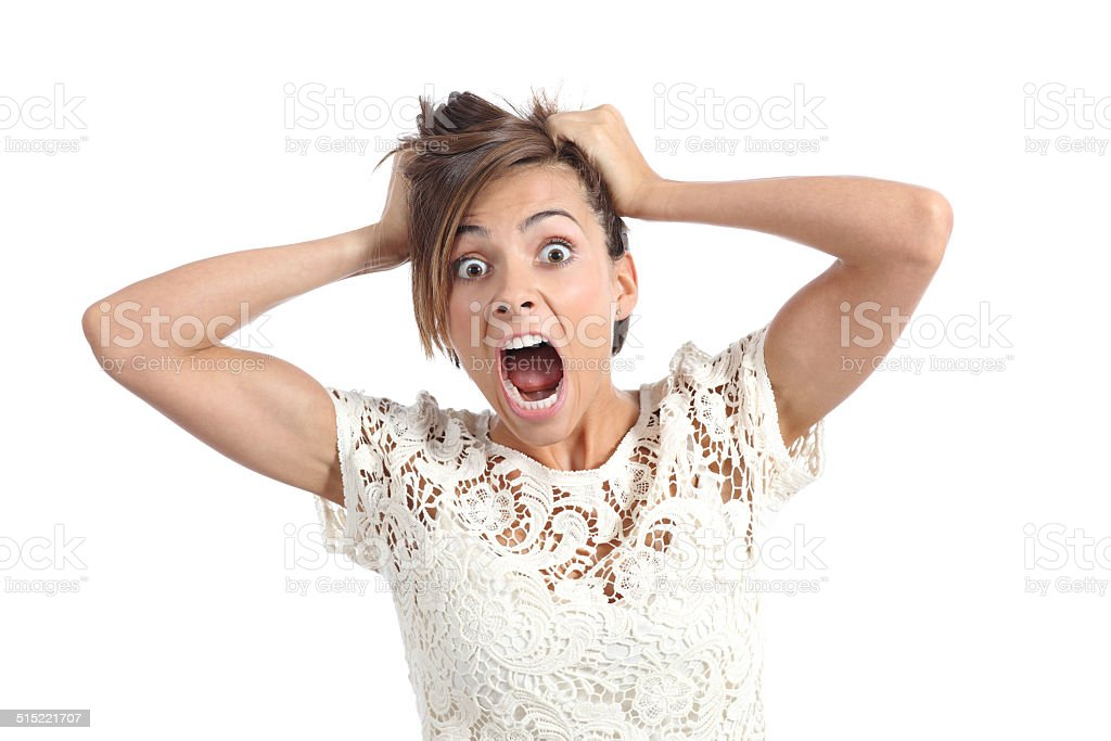 Scared woman screaming with hands on head stock photo