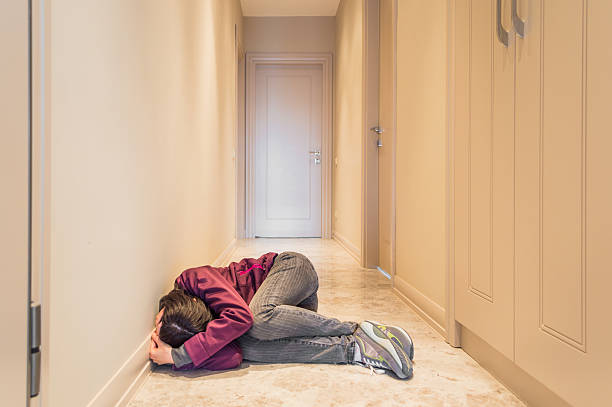 Scared Woman Sitting on the Floor Alone stock photo