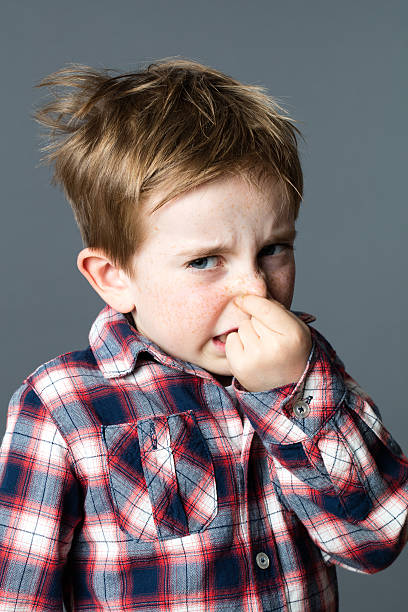 scared young kid pinching his nose annoyed by bad odor stock photo