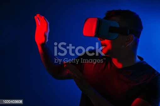 Scared young man in vr 3d glasses on dark background with red blue lighting.