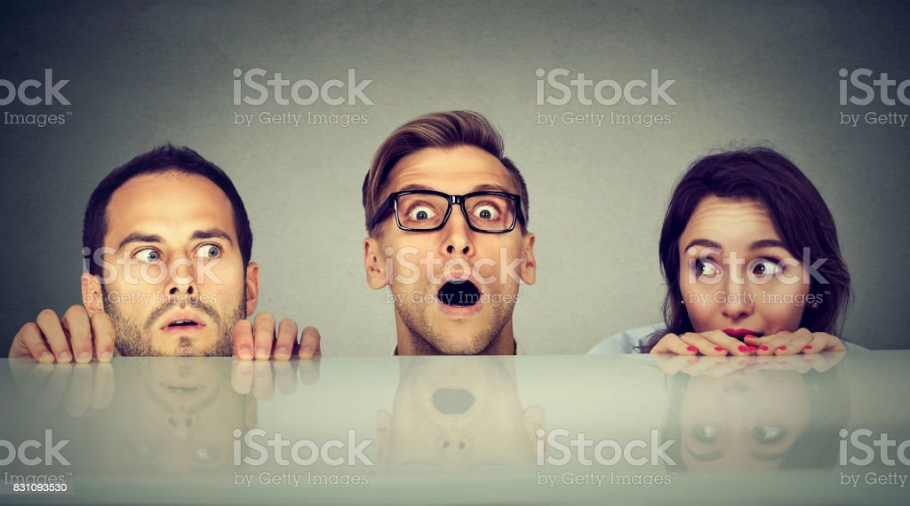 Scared young people two men and a woman hiding peeking form under the table stock photo