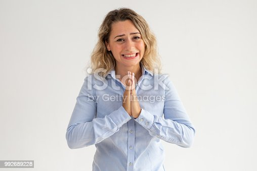 Scared young woman holding hands together and begging. Upset curly-haired female employee praying and asking about forgiveness. Despair concept