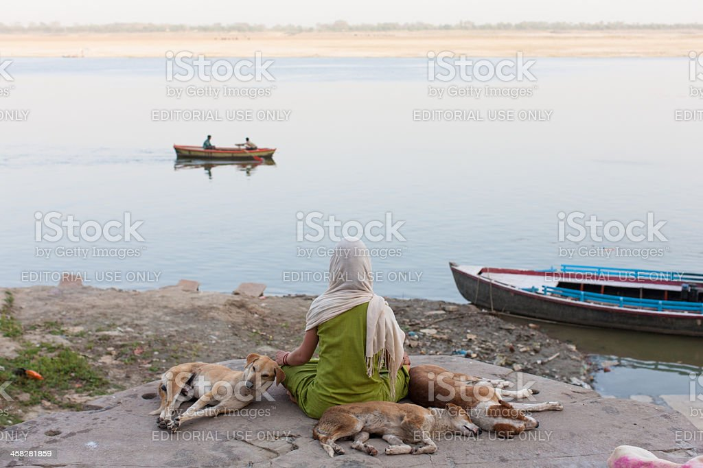 Scarfed young woman meditating on the Ganges border foto