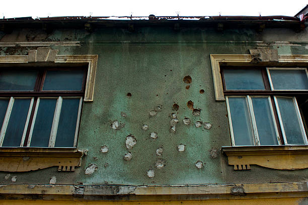 Scars of war in Mostar A bullet riddled builing in downtown Mostar, Bosnia. mass murder stock pictures, royalty-free photos & images