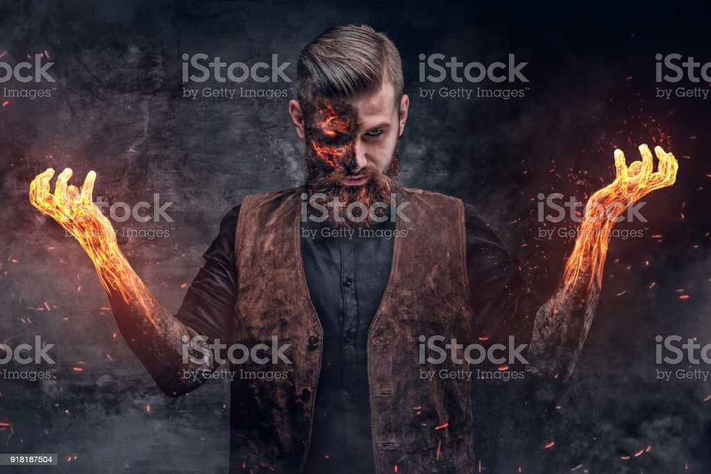 Scary burning man with arms in a fire. stock photo
