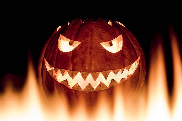 scary carved halloween pumpkin in hot burning hell fire flames - demoniac stock pictures, royalty-free photos & images